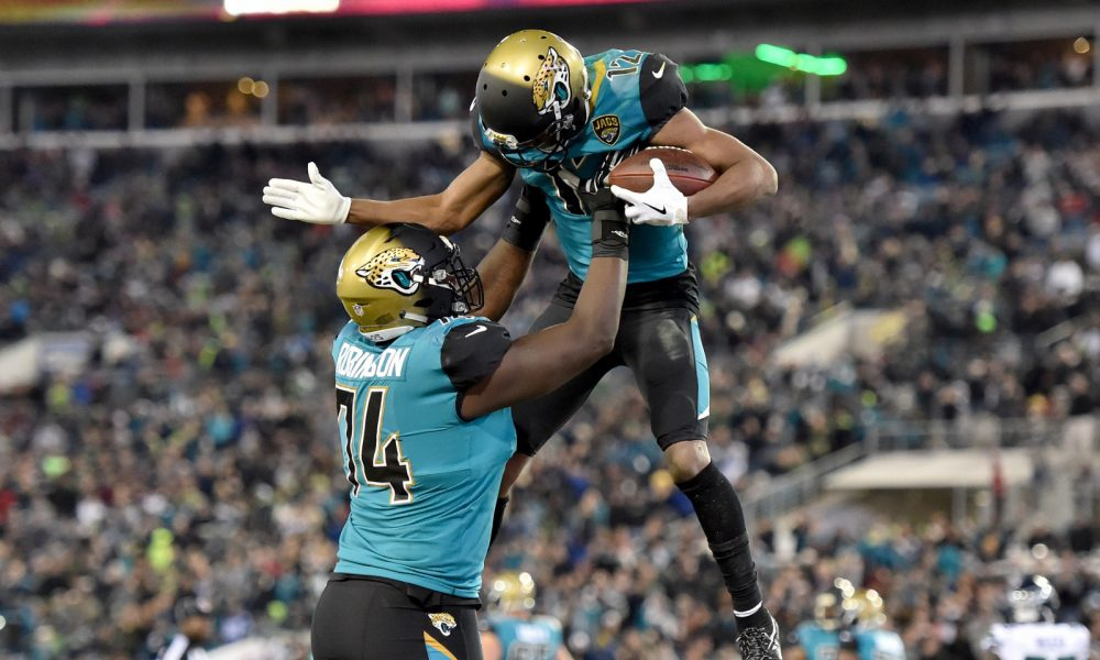 Cam Robinson lifting Dede Westbrook in 2017 after a touchdown