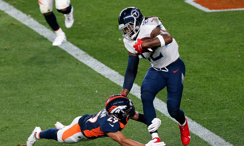 Derrick Henry runs through a tackle of Denver Broncos defender
