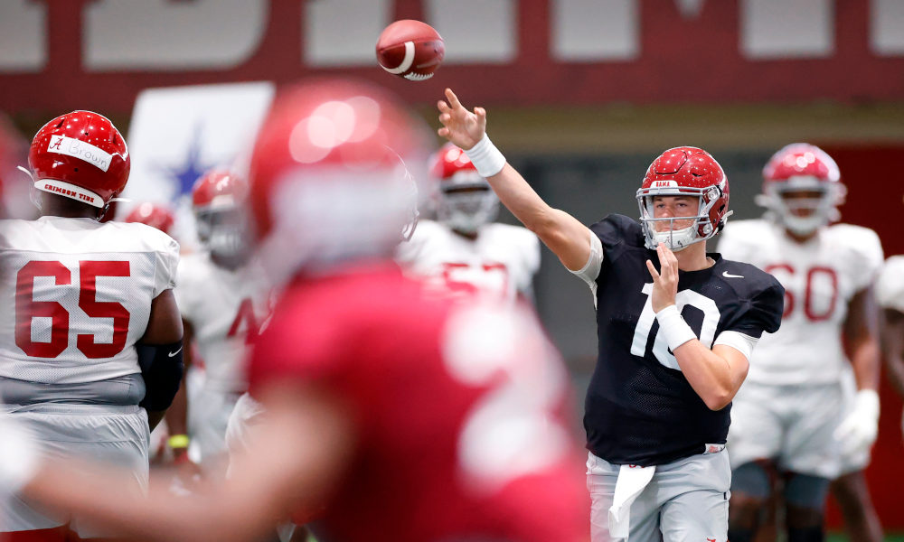 Mac Jones throws the ball indoors during an Alabama fall camp practice