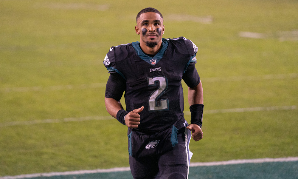 Jalen Hurts runs off the field in celebrating a win for Eagles in his first start