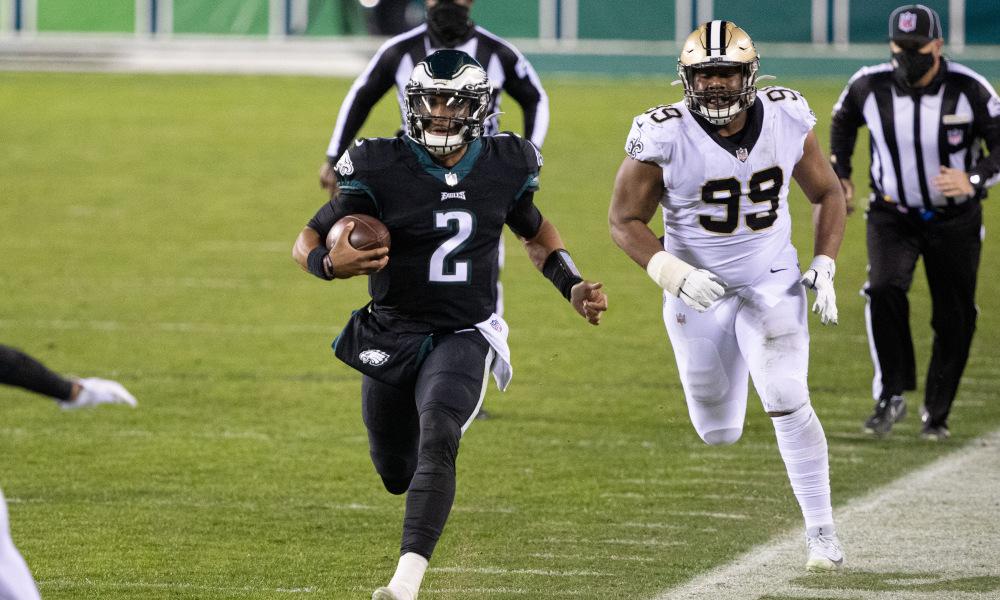 Jalen Hurts runs away from a Saints defender