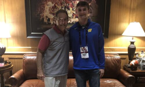 Ty Simpson takes a picture with nick Saban